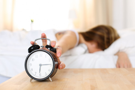 despertarse: Mujer joven soñoliento tratando despertador matanza mientras que enterrar la cara en la almohada. Temprano despertar, no dormir lo suficiente, conseguir el concepto de trabajo. Mano femenina que se extiende a sonar la alarma a su vez dispuesto apagado