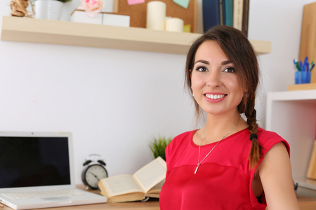 exam room: Beautiful smiling female student sitting in her room half turn studying. Young brunette woman in red dress at workplace with laptop and opened book preparing for exams. Education and self development Stock Photo