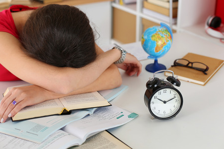 Tired female student at workplace in room taking nap on pile of textbooks. Sleepy brunette woman resting during education after sleepless night. Student in despair caused by exam deadline concept