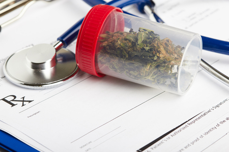 Medical marijuana in jar lying on prescription form near stethoscope. Cannabis recipe for personal use. Legal drugs concept
