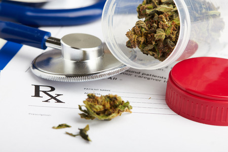 marijuana: Medical marijuana in jar lying on prescription form near stethoscope. Cannabis recipe for personal use. Legal drugs concept