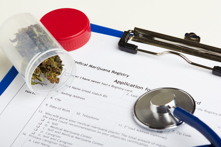 marijuana plant: Medical marijuana in jar lying on prescription form near stethoscope. Cannabis recipe for personal use. Legal drugs concept
