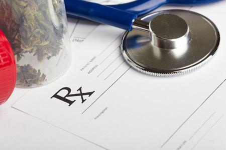 medical doctor: Medical marijuana in jar lying on prescription form near stethoscope. Cannabis recipe for personal use. Legal drugs concept