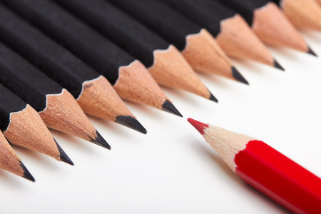 standing out from the crowd: Red pencil standing out from crowd of plenty identical black fellows on white table. Stock Photo