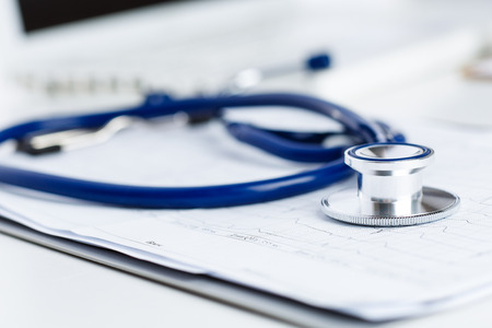 diagnosing: Medical stethoscope lying on cardiogram chart closeup.