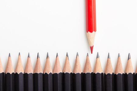 빨간색 연필 화이트 테이블에 많은 동일한 검은 휄 로우의 군중에서 밖으로 서.