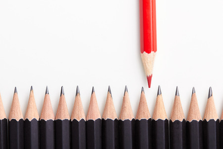 Rood potlood staande uit menigte van veel identieke zwarte medemensen op witte lijst. Stockfoto