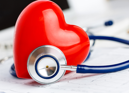 red stethoscope: Medical stethoscope head and red toy heart lying on cardiogram chart closeup. Stock Photo