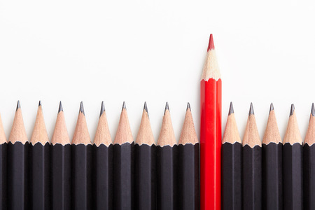 Red pencil standing out from crowd of plenty identical black fellows on white table.