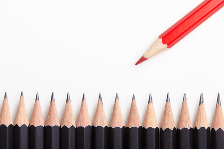 red pencil: Red pencil standing out from crowd of plenty identical black fellows on white table.