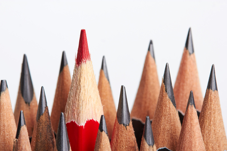 unique: Red pencil standing out from crowd of plenty identical black fellows on white table.