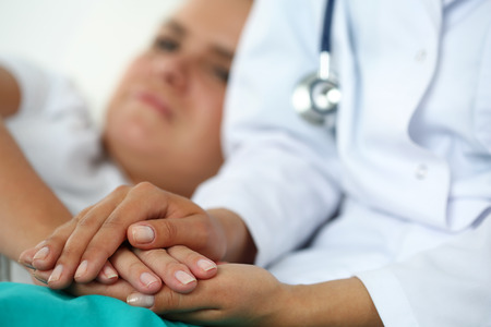Friendly female doctor hands holding patient hand lying in bed for encouragement