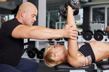 Personal trainer helping blonde woman in press of dumbbells.