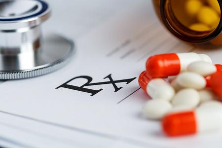 farmacia: Forma de prescripción se extiende a mesa con el estetoscopio, la pluma y la pila de pastillas se cayó del tarro. Formulario médico vacío listo para ser utilizado. Medicina o concepto farmacia. Los comprimidos y receta Foto de archivo