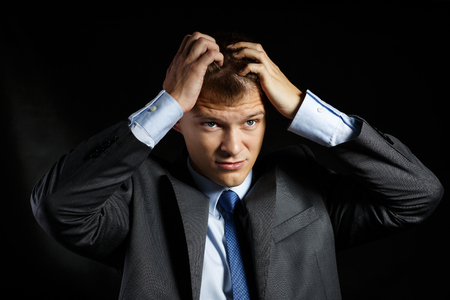 business concern: Businessman in suit tearing his hair with hands overloaded with troubles and headache standing over dark background. Business problems, stress, depression, concern and head ache concept Stock Photo