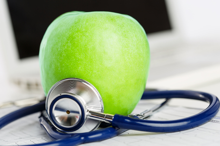 natural medicine: Green ripe fresh tasty apple lying on cardiogram chart surrounded with stethoscope. Stock Photo