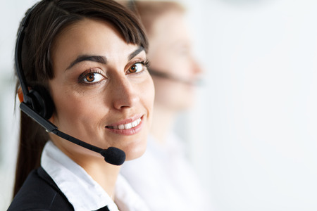 Female call center service operator at work. Portrait of smiling pretty female help-desk employee with headset at workplace.  Stock Photo