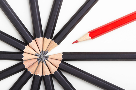 Red pencil standing out from crowd of plenty identical black fellows on white table. Leadership, uniqueness, independence, initiative, strategy, dissent, think different, business success concept 스톡 콘텐츠