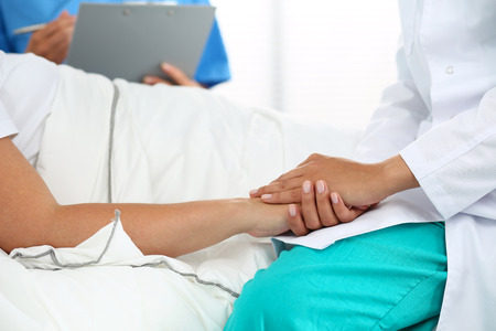 the patient: Friendly female doctor hands holding patient hand lying in bed for encouragement
