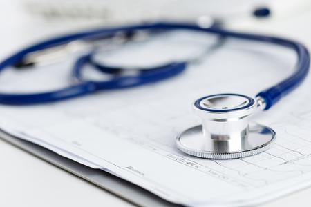 stethoscope: Medical stethoscope lying on cardiogram chart closeup.