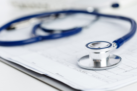 Medical stethoscope lying on cardiogram chart closeup.