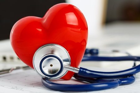 Medical stethoscope head and red toy heart lying on cardiogram chart closeup. Фото со стока