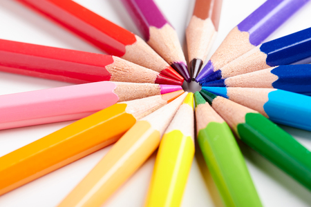 Set of multicoloured pencils lying on white table round order.