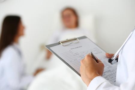 Vrouwelijke arts geneeskunde invullen van de patiënt medische geschiedenis lijst tijdens zaalronde terwijl patiënt communicatie met arts.