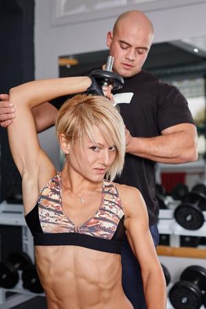 cuerpo femenino perfecto: Entrenador personal ayudando a la mujer rubia en prensa de pesas. Foto de archivo