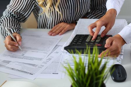세금 양식 완료 손을 근접 촬영을 위해 계산기 소득에 계산 두 여성 회계사. 금융 문서를 확인 국세청 관리자. 예산 계획, 감사 개념 스톡 콘텐츠