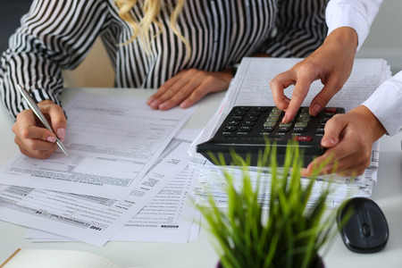 financial audit: Two female accountants counting on calculator income for tax form completion hands closeup. Internal Revenue Service inspector checking financial document. Planning budget, audit concept