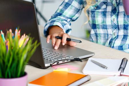 디지털 그래픽 태블릿 및 노트북을 사용하는 사무실에서 여성 디자이너의 손입니다. 사진 retoucher에 책상에 앉아 화면을보고. 창조적 인 사람이나 광고 스톡 콘텐츠