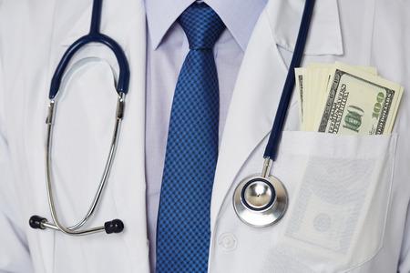 medicina: Hombre botiquín médico con montón de cien dólares billetes en el bolsillo de cerca. Medic sueldos de personal, el prestigio y alto trabajo remunerado, educación, negocio de la salud pública, el concepto de seguro médico Foto de archivo