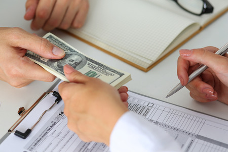 venality: Male hand taking or giving bunch of hundred dollars bank notes to woman closeup. Female hand accepting cash payment from man. IRS, bribe and bribery, collusion, crime, revenue report concept Stock Photo