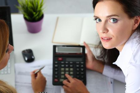 auditoría: Dos contadores femeninos contando con ingresos calculadora para completar el formulario de impuestos del primer. Interna inspector del Servicio de Impuestos comprobación documento financiero. Planificación de presupuesto, auditoría, concepto de seguro