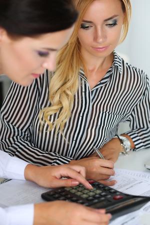 auditoría: Dos contadores femeninos contando con ingresos calculadora para el formulario de impuestos de finalización primer de las manos. Interna inspector del Servicio de Impuestos comprobación documento financiero. Planificación de presupuesto, el concepto de auditoría Foto de archivo