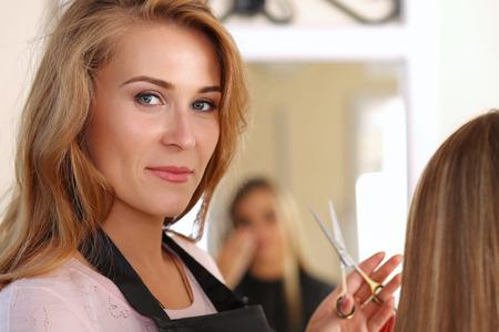 peluqueria: Peluquero hermoso mujer rubia con tijeras en las manos, recogiendo peinado propio de larga cliente pelo y mirando a puerta cerrada. Salón de peluquería, barbería, aspecto perfecto, nuevo concepto de peinado