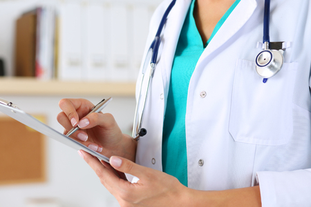 doctor examine: Female medicine doctor hand holding silver pen writing something on clipboard closeup. Medical care, insurance, prescription, paper work or career concept. Physician ready to examine patient and help