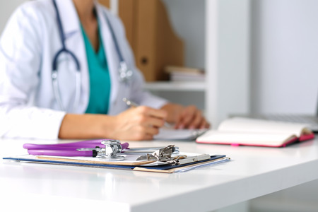 Stethoscope head lying on medical forms on clipboards closeup while medicine doctor working in background. Health care, insurance and help concept. Physician ready to examine patient