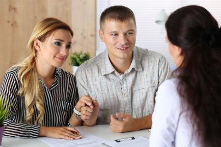 Giovane coppia famiglia cercando di ottenere il prestito in banca impiegato d'ufficio. Marito e moglie chiedendo ufficiale di servizio sociale per il permesso di adozione del bambino. Pianificazione futura, la vita coniugale, aspettativa, concetto mutuo