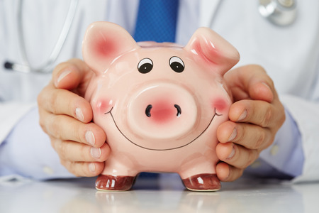 Male medicine doctor wearing blue tie holding and covering happy funny smiling piggybank in hands closeup. Medical service economy, health care savings and insurance concept. Focus on piggy bank