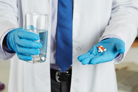 medical insurance: Male medicine doctor hands in blue gloves holding and offering pile of pills and glass of water. Medical care, prescription, pharmacology, insurance concept. Giving or showing medications to patient Stock Photo