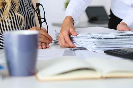 사무실에서 두 여자의 손입니다. 집행자에게 여분의 작업을주는 매니저 또는 상사에게 문서의 팩을 보여주는 직원. 과로, 초과 근무, 마감일, 서류 작 스톡 콘텐츠