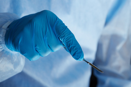 reanimować: Surgeon hand holding surgical scalpel while operating patient in surgical theatre closeup. Resuscitation medicine team holding steel medical tools saving patient. Surgery and emergency concept