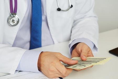 salud publica: Doctor de sexo masculino medicina sosteniendo en las manos puñado de cien dólares billetes contarlos. Medic sueldos de personal, el prestigio y alto trabajo remunerado, educación, negocio de la salud pública, el concepto de seguro médico
