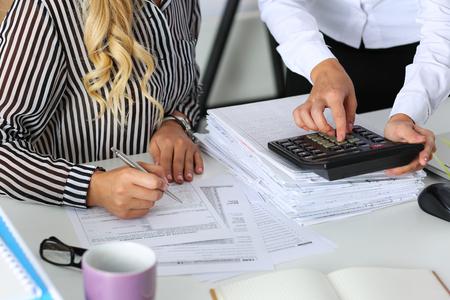 impuestos: Dos contadores femeninos contando con ingresos calculadora para el formulario de impuestos de finalización primer de las manos. Interna inspector del Servicio de Impuestos comprobación documento financiero. Planificación de presupuesto, el concepto de auditoría Foto de archivo