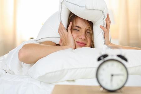 Giovane bella donna bionda che si trova nel letto a causa di suono della sveglia che copre testa e le orecchie con il cuscino che fa fronte sgradevole. All'inizio svegliarsi, non dormire a sufficienza, andando concetto di lavoro