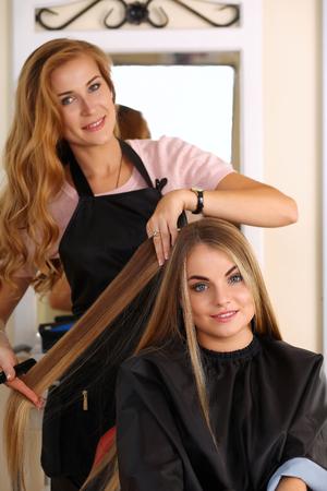 peluquero: Hermosa rubia mujer la celebraci�n de peluquer�a peine y bloqueo del pelo, haciendo nuevo peinado de la mujer al cliente muy sonriente con el libro de la muestra en las manos. Sal�n de peluquer�a, barber�a, perfecto concepto vistazo