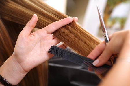 tinte cabello: asimiento femenino del peluquero en la mano entre los dedos mechón de pelo, peine y tijeras de oro de cerca. salón de peluquería, barbería, aspecto perfecto, nuevo peinado y el color, el concepto de enderezamiento