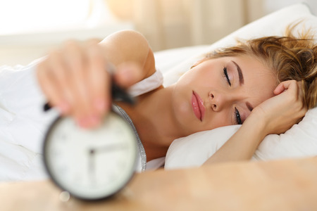 willing: Sleepy young woman portrait with one opened eye trying kill alarm clock. Early wake up, not getting enough sleep, going work concept. Female stretching hand to ringing alarm willing turn it off Stock Photo